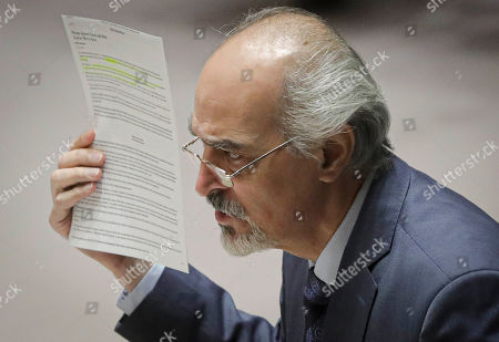 Syria's United Nations Ambassador Bashar Jaafari display an article as he address a U.N. Security Council meeting on Syria, at U.N. headquarters