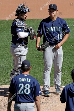 Seattle Mariners starting pitcher Yusei Kikuchi (18) waits with catcher Omar Narvaez, left, as they wait for visit from pitching coach Paul Davis (28) during the fourth inning of a baseball game against the Pittsburgh Pirates in Pittsburgh
