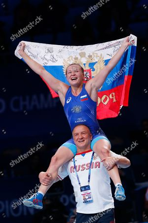 Inna Trazhukova of Russia, top, celebrates as she won the gold match of the women's 65kg category against Iryna Koliadenko of Ukraine during the Wrestling World Championships in Nur-Sultan, Kazakhstan