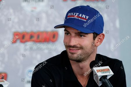 Alexander Rossi smiles during a news conference for an IndyCar Series auto race at Pocono Raceway, in Long Pond, Pa. Josef Newgarden leads Rossi in the IndyCar standings heading into this weekend's finale at Laguna Seca Raceway in Monterey, Calif