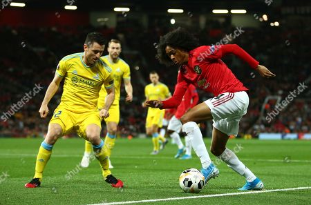 Astana's Antonio Rukavina, left, competes for the ball with Manchester United's Tahith Chong during the Europa League Group L soccer match between Manchester United and Astana at Old Trafford stadium in Manchester, England