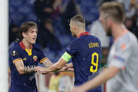 Roma's Edin Dzeko, center, celebrates with his teammate Nicolo Zaniolo, left, after he scored his side's second goal during a group J Europa League soccer match between Roma and Istanbul Basaksehir, at Rome's Olympic Stadium