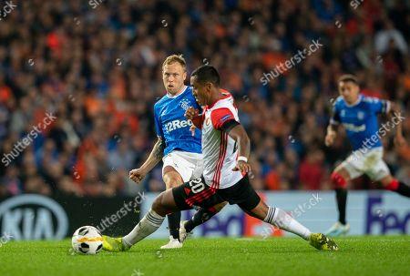 Scott Arfield of Rangers passes the ball beyond Renato Tapia of Feynoord.