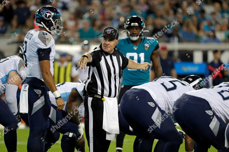 Umpire Paul King, center, has a discussion with Tennessee Titans quarterback Marcus Mariota, left, before a play during the first half of an NFL football game between the Jacksonville Jaguars and the Tennessee Titans, in Jacksonville, Fla