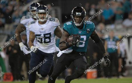 Jacksonville Jaguars wide receiver Chris Conley (18) runs away from Tennessee Titans linebacker Harold Landry (58) during the second half of an NFL football game, in Jacksonville, Fla