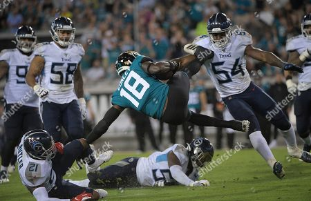 Jacksonville Jaguars wide receiver Chris Conley (18) gets sent flying by Tennessee Titans inside linebacker Rashaan Evans (54) during the second half of an NFL football game, in Jacksonville, Fla