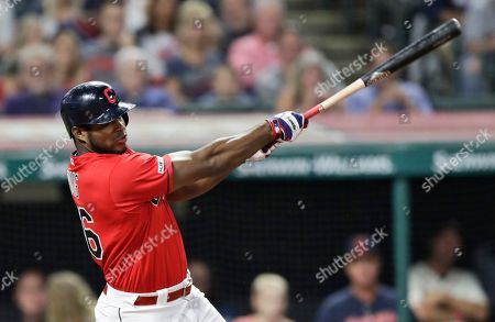 Cleveland Indians' Yasiel Puig hits a one-run double in the fourth inning in a baseball game against the Detroit Tigers, in Cleveland. Carlos Santana scored on the play