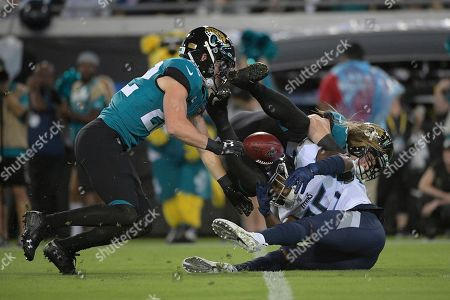 Tennessee Titans cornerback Adoree' Jackson (25) fumbles the football after getting hit by Jacksonville Jaguars defensive back Andrew Wingard (42) and defensive back Cody Davis (22) during the first half of an NFL football game, in Jacksonville, Fla