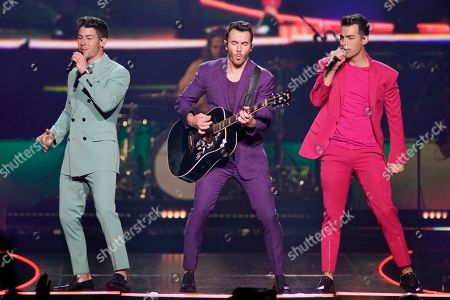"Nick Jonas, Kevin Jonas, Joe Jonas. Nick Jonas, from left, Kevin Jonas, and Joe Jonas, of The Jonas Brothers, perform during their ""Happiness Begins Tour"" at the United Center, in Chicago"