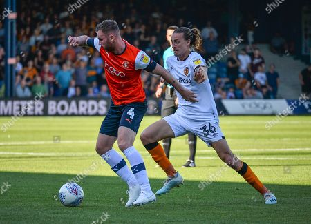 Ryan Tunnicliffe of Luton Town holds off Jackson Irvine of Hull City