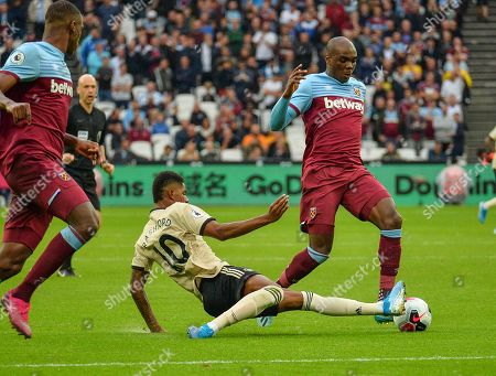 Marcus Rashford of Manchester United makes a sliding tackle on Angelo Ogbonna of West Ham United