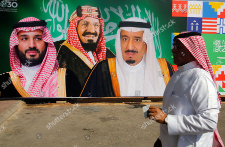 "A man walks in front of a banner showing Saudi King Salman, right, his Crown Prince Mohammed bin Salman, left, and Saudi Arabia's founder late King Abdul Aziz Al Saud, center, at the private airport in Riyadh, Saudi Arabia, . Any attack on Iran by the U.S. or Saudi Arabia will spark an ""all-out war,"" Tehran's top diplomat warned Thursday, raising the stakes as Washington and Riyadh weigh a response to a drone-and-missile strike on the kingdom's oil industry that shook global energy markets"
