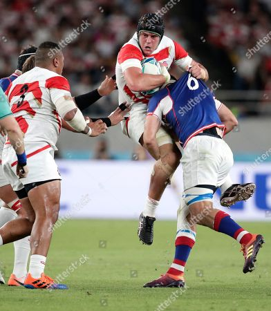 Japan's James Moore is tackled by Russia's Vitaly Zhivatov during the Rugby World Cup Pool A game at Tokyo Stadium between Russia and Japan in Tokyo, Japan