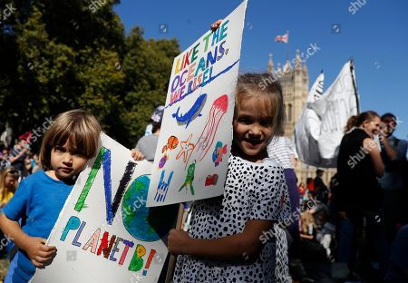 Stock Image of Lola and Peter Jones hold up their banners as they take part in a climate protest near Parliament in London, . Protesters around the world joined rallies on Friday as a day of worldwide demonstrations calling for action against climate change began ahead of a U.N. summit in New York