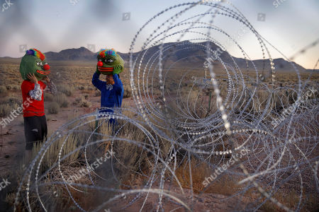"Stock Picture of Martin Custodio, left, and Rafael Castillo wear Pepe masks while standing near razor wire at an entrance to the Nevada Test and Training Range near Area 51, near Rachel, Nev. People came to visit the gate inspired by the ""Storm Area 51"" internet hoax"