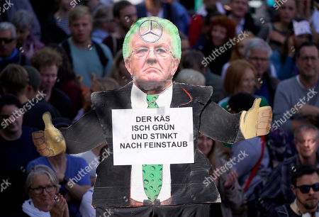 Students hold a placard showing the Prime Minister of Baden-Wuerttemberg Winfried Kretschmann as they take part in a globale demonstration against climate change in Stuttgart, Germany, 20 September 2019. Youth and students across the world are taking part in a student strike movement called Friday For Future which was sparked by Greta Thunberg of Sweden, a sixteen year old climate activist who has been protesting outside the Swedish parliament every Friday since August 2018. The sign reads 'The cheese is green and smells of fine dust.'