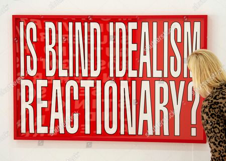 Stock Picture of A woman stands in front of the work 'Is blind idealism reactionary?' (2011) by Barbara Kruger during the press preview for the exhibition 'Barbara Kruger' in Goslar, Germany, . The 73-year-old American conceptual artist Barbara Kruger receives the Goslar Kaiserring Award 2019 in Goslar on Saturday, Sept. 21, 2019. The undoped Kaiserring is considered one of the most important international awards for modern art. The exhibition starts on Sept. 21, 2019 and lasts until Jan. 26, 2020