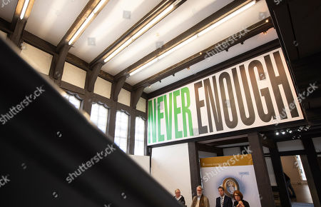 People sit under a poster during the press conference prior the press preview for the exhibition 'Barbara Kruger' in Goslar, Germany, . The 73-year-old American conceptual artist Barbara Kruger receives the Goslar Kaiserring Award 2019 of Goslar in Saturday, Sept. 21, 2019. The undoped Kaiserring is considered one of the most important international awards for modern art. The exhibition starts on Sept. 21, 2019 and lasts until Jan. 26, 2020