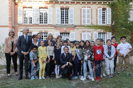 Stock Picture of French President Emmanuel Macron (C), his wife Brigitte Macron (5thL), French Culture Minister Franck Riester (2ndL) and French TV host Macron's and cultural special adviser Stephane Bern (4thL) pose for a picture with pupils visiting the Chateau de By ('By Castle'), the former property of the late French artist Rosa Bonheur, in Thomery, outside Paris, France, 20 September 2019. In support of the European Heritage Days, Emmanuel and Brigitte Macron visited the residence of the painter Rosa Bonheur on September 20, one of the emblematic projects that receive financial support from the heritage mission. The French Ministry of Culture has selected 18 emblematic sites to profit from the 'Loto du patrimoine' draw.