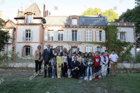 Stock Photo of French President Emmanuel Macron (C), his wife Brigitte Macron (5thL), French Culture Minister Franck Riester (2ndL) and French TV host Macron's and cultural special adviser Stephane Bern (4thL) pose for a picture with pupils visiting the Chateau de By ('By Castle'), the former property of the late French artist Rosa Bonheur, in Thomery, outside Paris, France, 20 September 2019. In support of the European Heritage Days, Emmanuel and Brigitte Macron visited the residence of the painter Rosa Bonheur on September 20, one of the emblematic projects that receive financial support from the heritage mission. The French Ministry of Culture has selected 18 emblematic sites to profit from the 'Loto du patrimoine' draw.