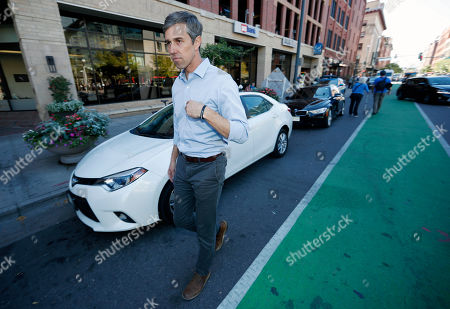 Stock Photo of R m. U.S. Rep. Beto O'Rourke, D-Texas, heads to a waiting vehicle after greeting participants in a global climate change march, through downtown Denver. The world over, both young and old have banded together to demand action from leaders to combat climate change