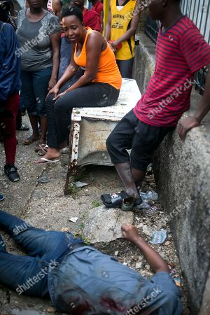 A distraught relative of Rigueur Pierre Richard, who was killed in a drive-by shooting two blocks from the national palace, sits next to his body, during a protest against fuel shortages and demanding the resignation of President Jovenel Moise in Port-au-Prince, Haiti, . According to witnesses, two other people were injured in the attack. Haiti remains at a standstill with no public transportation available and banks, government offices, and schools closed amid street protests due to an ongoing fuel crisis