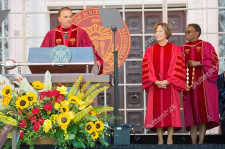 Interim USC President Wanda Austin, right, and USC Board of Trustees Chair Rick Caruso, left, bestow USC President Carol L. Folt with the Medal of Office during her inauguration in Los Angeles