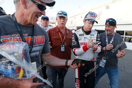 Brad Keselowski, second from right, gives autographs after winning the pole for a NASCAR Monster Energy Cup auto race at Richmond Raceway in Richmond, Va