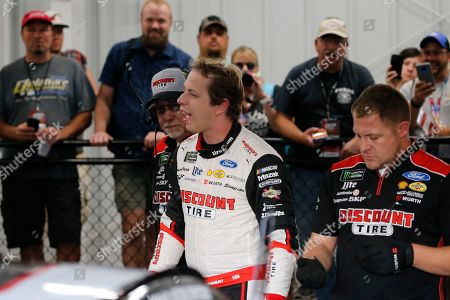 Brad Keselowski, front center, smiles in the garage after winning the pole for the NASCAR Cup Series auto race at Richmond Raceway in Richmond, Va