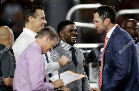 Brady Quinn, Reggie Bush, Matt Leinart. Former college and NFL players from left in back, Brady Quinn, Reggie Bush, and Matt Leinart joke while standing near the end zone during the second half of an NCAA college football game between Southern California and Utah, in Los Angeles