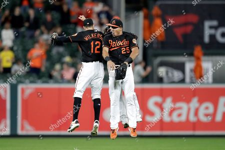 Baltimore Orioles outfielders Stevie Wilkerson (12) Anthony Santander (25) and Austin Hays celebrate after defeating the Seattle Mariners during a baseball game, in Baltimore