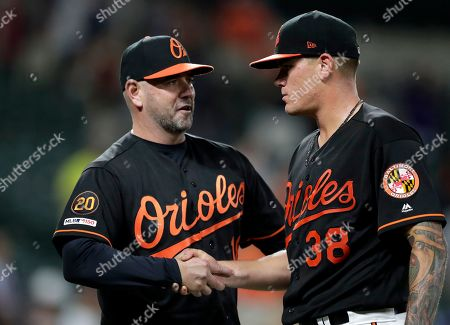 Baltimore Orioles manager Brandon Hyde, left, shakes hands with pitcher Aaron Brooks (38) while celebrating after defeating the Seattle Mariners in a baseball game, in Baltimore