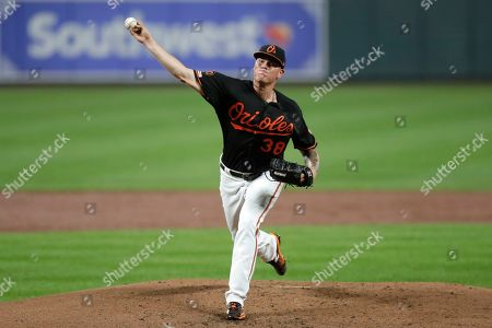 Baltimore Orioles starting pitcher Aaron Brooks throws a pitch to a Seattle Mariners batter during the third inning of a baseball game, in Baltimore