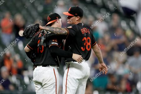 Baltimore Orioles catcher Chance Sisco (15) and pitcher Aaron Brooks (38) celebrate after defeating the Seattle Mariners in a baseball game, in Baltimore