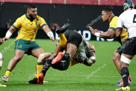 Australia's Tolu Latu, left, and Scott Sio right, watch as teammate David Pocock tackles a Fijian attacker during the Rugby World Cup Pool D game at Sapporo Dome between Australia and Fiji in Sapporo, Japan