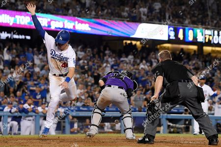 Gavin Lux, Enrique Hernandez, Greg Gibson. Los Angeles Dodgers' Gavin Lux, left, trips over Colorado Rockies catcher Tony Wolters, center, as he scores on a single by Enrique Hernandez while home plate umpire Greg Gibson watches during the seventh inning of a baseball game, in Los Angeles