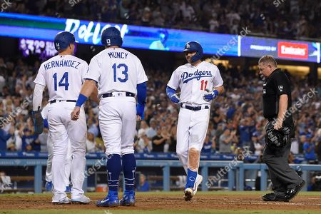 A.J. Pollock, Enrique Hernandez, Max Muncy, Greg Gibson. Los Angeles Dodgers' A.J. Pollock scores after hitting a three-run home run against the Colorado Rockies, as Enrique Hernandez, left, and Max Muncy, second from left, wait for him while home plate umpire Greg Gibson stands at the plate during the fourth inning of a baseball game, in Los Angeles