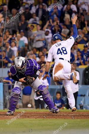 Gavin Lux, Enrique Hernandez. Los Angeles Dodgers' Gavin Lux, right, trips over Colorado Rockies catcher Tony Wolters as he scores on a single by Enrique Hernandez during the seventh inning of a baseball game, in Los Angeles