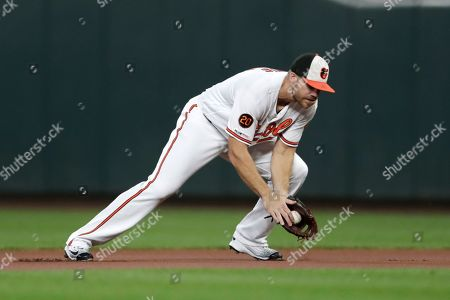 Baltimore Orioles first baseman Chris Davis fields a ground ball from a Toronto Blue Jays batter during the first inning of a baseball game, in Baltimore