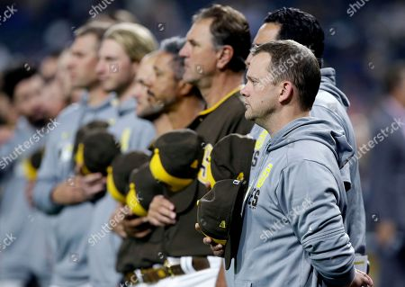 San Diego Padres manager Andy Green, right, stands with his team during the national anthem before a baseball game against the Arizona Diamondbacks in San Diego