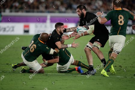 New Zealand's TJ Perenara pass the ball to teammate Samuel Whitelock, right, during the Rugby World Cup Pool B game at International Stadium between New Zealand and South Africa in Yokohama, Japan