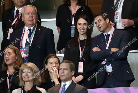 New Zealand Prime Minister Jacinda Ardern, centre, stands with her partner Clarke Gayford, right, and World Rugby Chairman Bill Beaumont, left, watch the Rugby World Cup Pool B game at International Stadium between New Zealand and South Africa in Yokohama, Japan