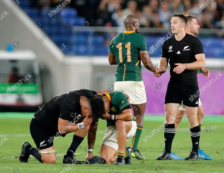 Artie Savea (L) of New Zealand kneels down with an unidentified South African for a prayer  as teammate Ben Smith (R) greets Makable Mapimpi (2-R) of South Africa after the Rugby World Cup 2019 match between New Zealand and South Africa in Yokohama, south of Tokyo, Japan, 21 September 2019.