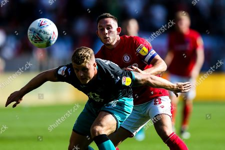 Tom Carroll of Swansea City is challenged by Josh Brownhill of Bristol City