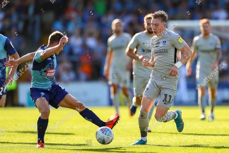 Stock Photo of Portsmouth midfielder Ronan Curtis (11) is challenged by Wycombe Wanderers midfielder Dominic Gape (4) during the EFL Sky Bet League 1 match between Wycombe Wanderers and Portsmouth at Adams Park, High Wycombe