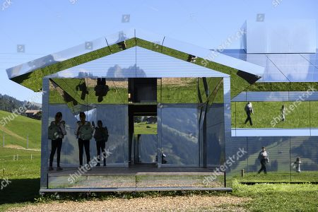 People visit the installation 'Mirage Gstaad' by American artist Doug Aitken, in Gstaad, Switzerland, 21 September 2019. The structure is presented during the exhibition 'Elevation 1049: Frequencies' that will be visible until spring 2021.
