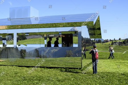 Stock Picture of People visit the installation 'Mirage Gstaad' by American artist Doug Aitken, in Gstaad, Switzerland, 21 September 2019. The structure is presented during the exhibition 'Elevation 1049: Frequencies' that will be visible until spring 2021.