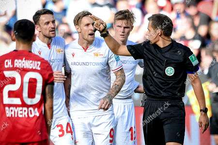 Union's Sebastian Polter (C) leaves the pitch after booking red card by referee Robert Hartmann (R) during the German Bundesliga soccer match between Bayer Leverkusen and 1. FC Union Berlin in Leverkusen, Germany, 21 September 2019.