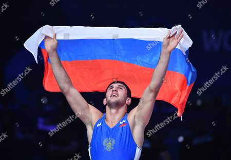 Zaurbek Sidakov of Russia holds a Russian national flag as he celebrates his victory over Frank Chamizo Marquez of Italy in their gold match of the men's 74kg category during the Wrestling World Championships in Nur-Sultan, Kazakhstan