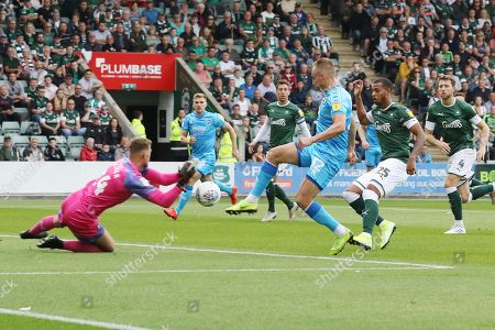 Alex Palmer saves under pressure from Luke Varney during the EFL Sky Bet League 2 match between Plymouth Argyle and Cheltenham Town at Home Park, Plymouth
